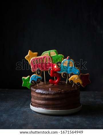 Chocolate cake decorated with gingerbread with the image of cars. Dark background, minimalism. #1671564949