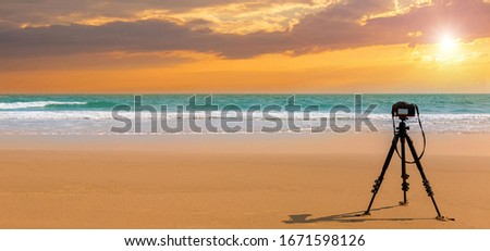 Digital professional camera stand on tripod photographing sea. Twilight sky background. Colorful Sunset sky and cloud.vivid sky in twilight time background.Fiery orange sunset sky. Beautiful