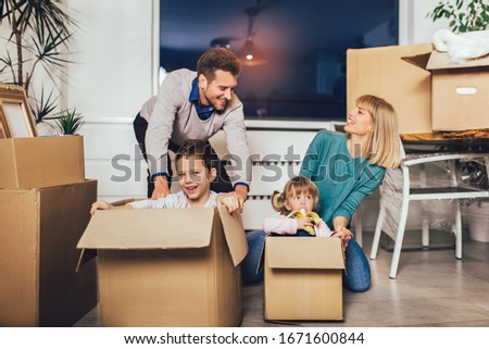 Happy family moving home with boxes around #1671600844