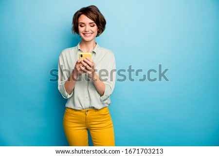 Photo of attractive lady holding telephone hands reading new blog post positive comments popular blogger wear casual green shirt yellow trousers isolated blue color background Royalty-Free Stock Photo #1671703213