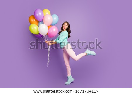 Full body photo of cheerful feminine girl hold many baloons enjoy festive woman day event scream wear turquoise pastel sweater pink footwear isolated over purple color background #1671704119