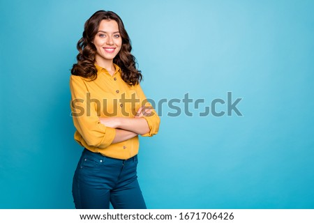 Photo of attractive curly business lady hold hands crossed toothy beaming smiling best chief worker wear yellow shirt trousers isolated blue color background