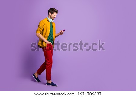 Full length body size side profile photo of cheerful positive handsome man brown haired with hands in trousers pocket holding telephone isolated pastel violet color background