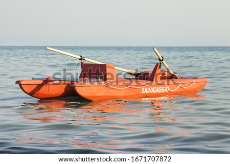 Italian boat rescue lifeguard. A lifeboat is in the water in the sea. Panorama with sea and sky in the background. Written Salvataggio (Rescue) on the side of the boat #1671707872