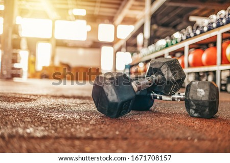Fitness and healthy background concept. Dumbbells with blurred gym or sport club background at sunset. Picture for add text message. Dumbbell in Fitness Room