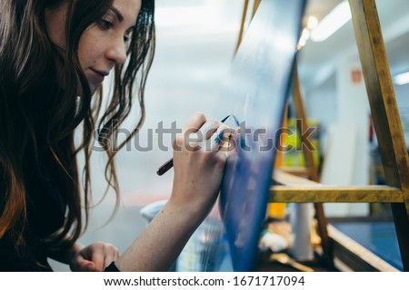 Close up portrait of beautiful and authentic young female artist or painter create art piece. Detailed work for personal creative project. Tattoo artist draws artwork #1671717094