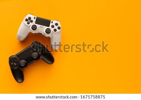 Stock photo of two gamepads on a yellow background and copy space on the right