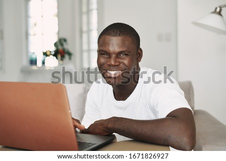 A cheerful man of African appearance sits at a table in front of a laptop chatting at home #1671826927