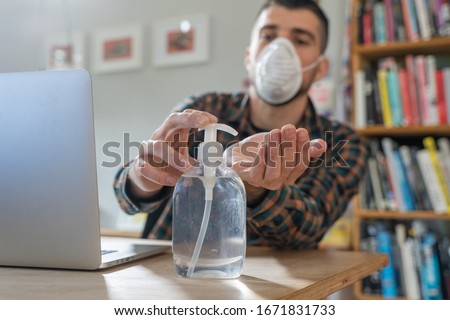 Coronavirus. Man working from home wearing protective mask. quarantine for coronavirus wearing protective mask. Working from home. Cleaning her hands with sanitizer gel.  Thermometer fever inspection. #1671831733