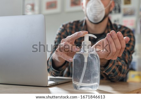 Coronavirus. Man working from home wearing protective mask. quarantine for coronavirus wearing protective mask. Working from home. Cleaning her hands with sanitizer gel.  Thermometer fever inspection. #1671846613