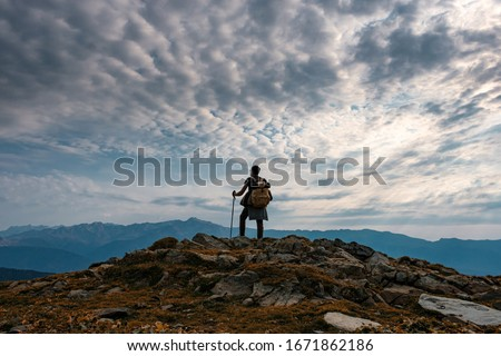 Young male hipster in the mountains in autumn. Discovery Travel Destination Concept. Tourist on the high rocks background. Sport and active life concept. Royalty-Free Stock Photo #1671862186