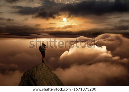 Girl Photographer Hiking on on a Rocky Mountain Peak with Beautiful and striking view of the puffy clouds during a colorful sunset or sunrise. Composite. Freedom, Lifestyle, Adventure, Hike, Explore