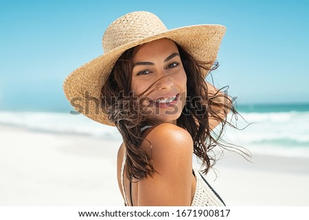Portrait of beautiful smiling young woman wearing straw hat at beach with sea in background. Beauty fashion girl looking at camera at seaside. Carefree tanned woman walking on sand and laughing. #1671900817
