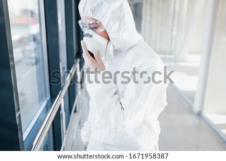 Female doctor scientist in lab coat, defensive eyewear and mask standing indoors. #1671958387