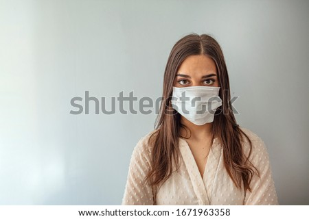 Woman in a medical mask close-up on a gray background. Healthy lifestyle, ill sick disease treatment concept. Mock up copy space. epidemic, dangerous and deadly virus, infection concept #1671963358