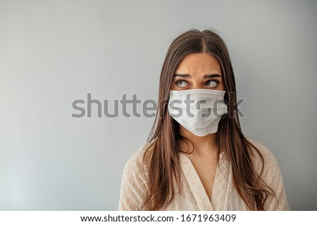 Woman wear with protective face mask. Young woman with face mask. Face of a mask-wearing woman with fear in the eye. Beautiful young woman wearing contamination mask at home #1671963409