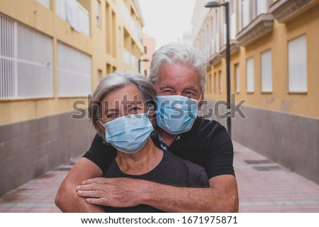 couple of two seniors wearing medical mask to prevent coronavirus (covid-19) or another type of virus - close up of faces in middle of street -  protect people satying safe together - italian people #1671975871