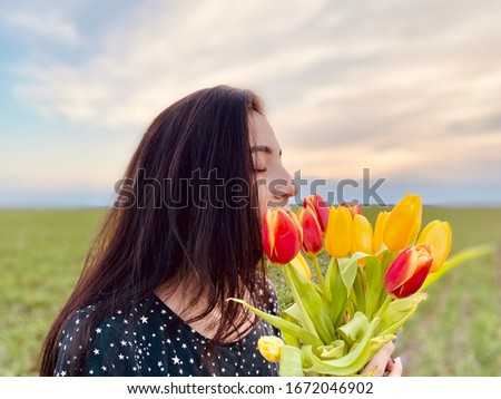 A girl in a summer dress smelling tulips #1672046902