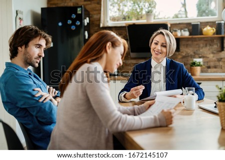 Happy real estate agent and young couple analyzing documents while having a meeting.  #1672145107