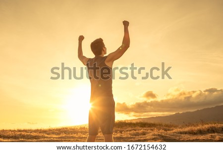Strong fit young man raising fist up the sunset sky. People victory and triumph.  Royalty-Free Stock Photo #1672154632
