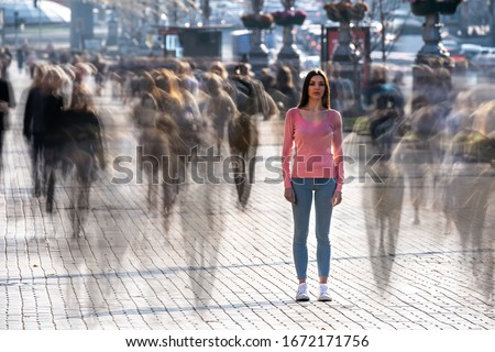 The young woman stands in the middle of crowded street Royalty-Free Stock Photo #1672171756