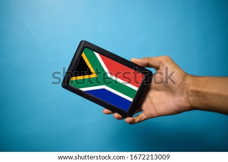 Man holding Smartphone with Flag of South Africa. South Africa Flag on Mobile Screen Isolated on Blue Background