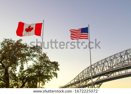 International Border Crossing. Sunset at the Blue Water Bridge border United States and Canada crossing. The bridge connects Port Huron, Michigan and Sarnia, Ontario. Royalty-Free Stock Photo #1672225072