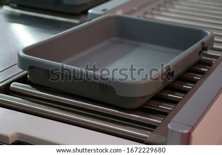 Closeup view of tray on conveyor of baggage and personnel belongings security scanner in airport                                #1672229680