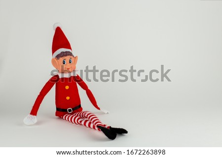Elf on a shelf on a white background. Royalty-Free Stock Photo #1672263898