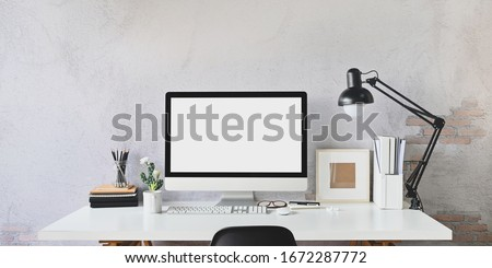 Workspace blank screen Computer and Equipment on table and loft wall background. Royalty-Free Stock Photo #1672287772