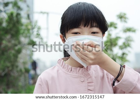 Coronavirus and Air pollution pm2.5 concept. A Chinese girl wearing a mask outdoors #1672315147