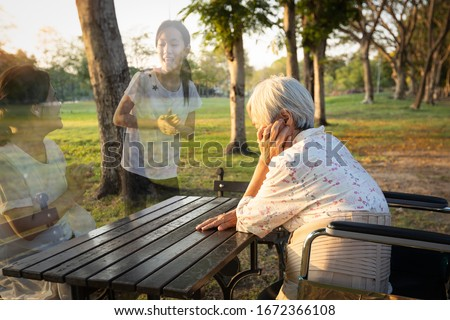 A lonely senior woman is waiting and thinking old memories of her family that will visit her again,depressed elderly people with loneliness and depression sitting alone,missing,nostalgia,remembrance Royalty-Free Stock Photo #1672366108