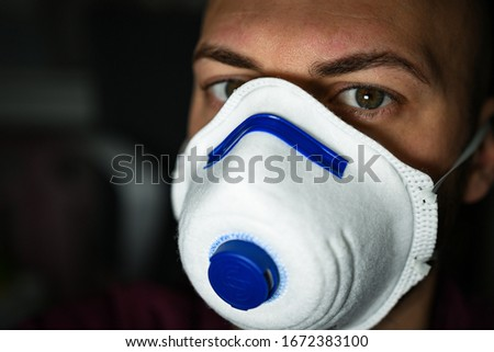 boy with green eyes and with a mask to avoid contagion from the Coronavirus COVID-19 #1672383100