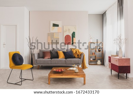 wooden coffee table and yellow chair in front of grey couch with pillows in trendy living room #1672433170