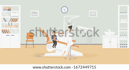 Interior of clinic: dentist's office with stylish medical equipment for dental treatment.Surgeon is talking to patient - little boy with Teddy bear.Products for oral hygiene in closet.Raster #1672449715