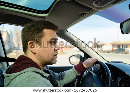 puzzled man in the grey sweater behind the wheel of the car rides and looks forward #1672457026