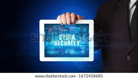 Young business person working on tablet and shows the digital sign: CYBER SECURITY #1672458685