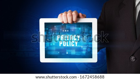Young business person working on tablet and shows the digital sign: PRIVACY POLICY #1672458688