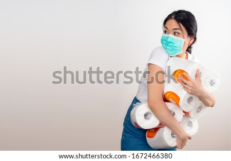 An Asian woman storing tissue toilet paper during Coronavirus outbreak or Covid-19, Concept of Covid-19 quarantine. Wuhan epidemic outbreak. Dangerous COVID virus, Doomsday panic people panic #1672466380