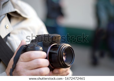 Outdoors photographer holds black digital camera and ready make a photo, focus point is on the lens #1672472461