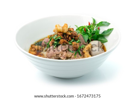 Rice Noodles Beef Soup with Beef,Liver, and Beef Ball ontop Crispy Fried Pork Skin ,Garlic and Stink Weed decorate Spring onions and Basil Thai herbs. Thai Boat Noodles Style sideview