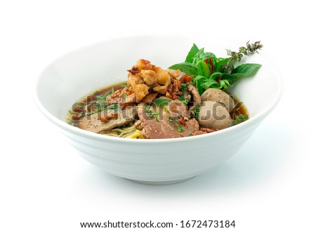 Egg Noodles Soup with Beef,Liver,Intestine Braised and Beef Ball ontop Crispy Fried Pork Skin,Garlic and Stink Weed decorate Spring onions and Basil Thai herbs. Thai Boat Noodles Style topview