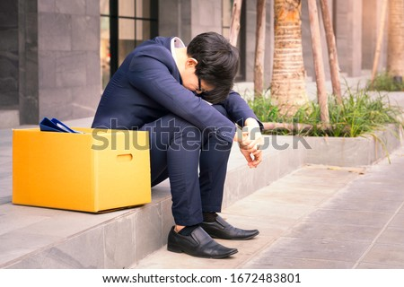 Unemployed man, The economic downturn made people unemployed, Desperate businessman sitting hopelessly on stair in central business district due to unemployment. failure, desperation, depression. #1672483801