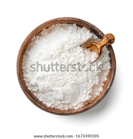 Wooden bowl with flour and flour spoon. Rice or wheat flour isolated on white background. top view #1672490305