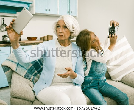 Grandma With Her Grandchild Use Each Other's Gadgets For Taking Selfie Pictures Senior Lady And Cheerful Girl Trying To Make Photo Session With Unusual Gadgets Sitting On Sofa At Home, Toned Image