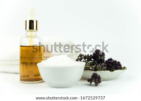 Spa treatment bottle of natural organic oil essence serum collagen. Towel, aromatic sea salt, herbs and flowers on white background. Copy space for text. Oil drop. #1672529737