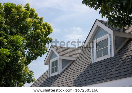 Roof shingles with garret house on top of the house among a lot of trees. dark asphalt tiles on the roof background Royalty-Free Stock Photo #1672585168