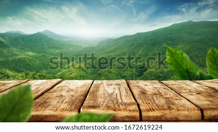 table background of free space for your decoration and blurred landscape of mountains.Blue sky with sun light and green small leaves.  #1672619224