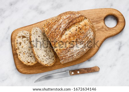 Round loaf of freshly baked sourdough bread with knife on cutting board, top view. Artisan bread with seeds on marble table. Rustic sourdough bread. #1672634146