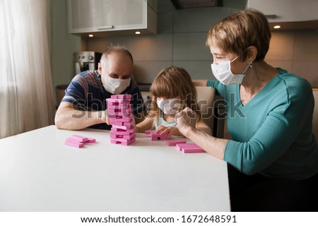 grandparents with granddaughter wearing medical face mask playing  board game together at home. quarantine. health concept. Corona Virus.  #1672648591